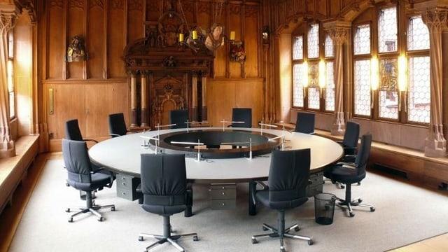 Blick in den Raum, wo die Basler Regierung tagt. Man sieht einen runden Tisch mit 10 Stühlen.