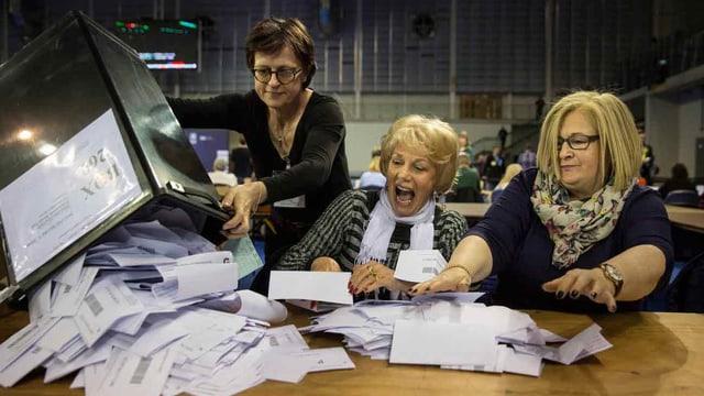 Frauen nehmen die Wahlzettel entgegen.
