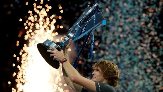 Giugader da tennis che auza si ina trofea.