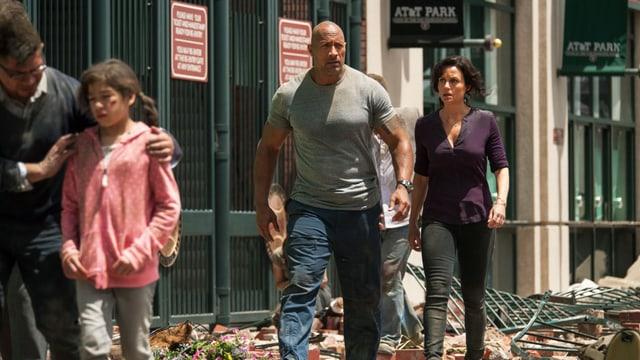 Dwayne Johnson und Carla Gugino laufen durch die zerstörte Stadt.