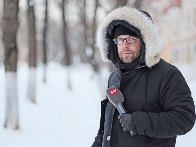 Korrespondent im Schnee mit Winterjacke und Kapuze.