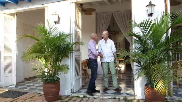 Zwei Männer geben sich in einem Hauseingang die Hand.