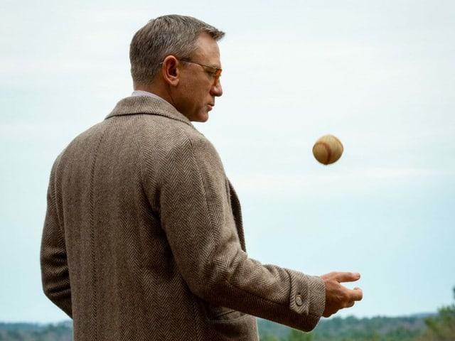 Ein Mann im Mantel spielt mit einem Baseball.