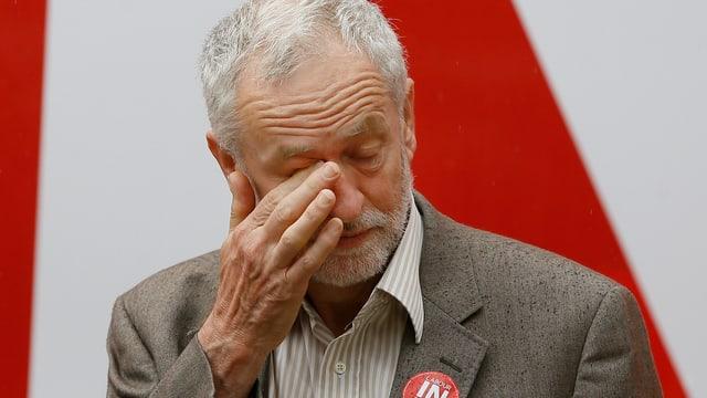 Labour-Chef Jeremy Corbyn reibt sich mit der rechten Hand das rechte Auge.