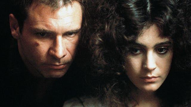 Ein Mann und eine Frau blicken ernst nach unten.