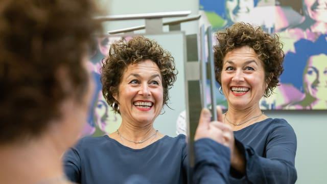 eine Frau mit kurzen Locken hält einen Spiegel hoch