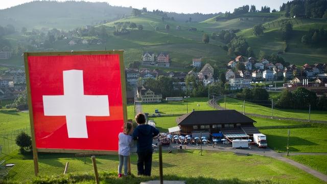 Blick auf Hügellandschaft. Im Vordergrund ist eine Schweizer Fahne zu sehen.