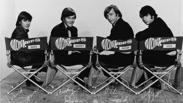 The Monkees sitzen auf Stühlen.