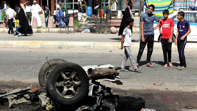 Die Reste eines Autos ausgebrannt auf der Strasse, Kinder und Jugendliche schauen zu, Passanten im Hintergrund.