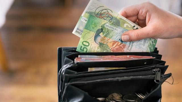 Eine Hand nimmt Geldnoten aus einem Portmonnaie.