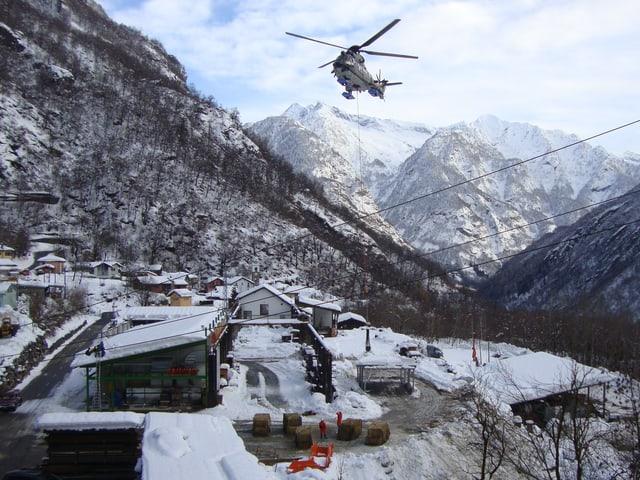 Ein Helikopter setzt Heuballen auf einem Parkplatz ab.