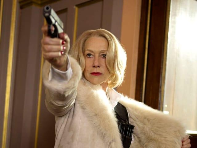 Frau in weissem Pelzmantel mit Pistole.
