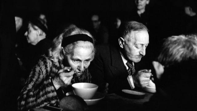 Schwarzweiss Aufnahme einer Frau (links) und eines Mannes, die eine Suppe essen.