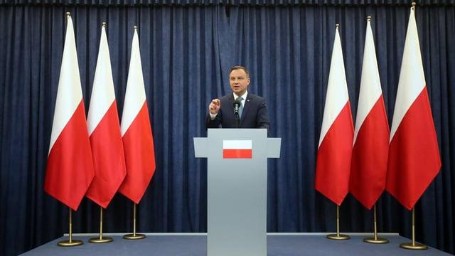 Staatspräsident Andrzej Duda an Rednerpult umrahmt von Polen-Fahnen