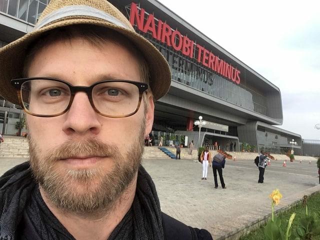 Selfie von Samuel Burri vor einem grossen Bahnhof.