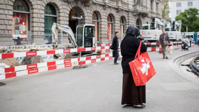 Frau mit Kopftuch mit grosser Tasche auf Trottoir.