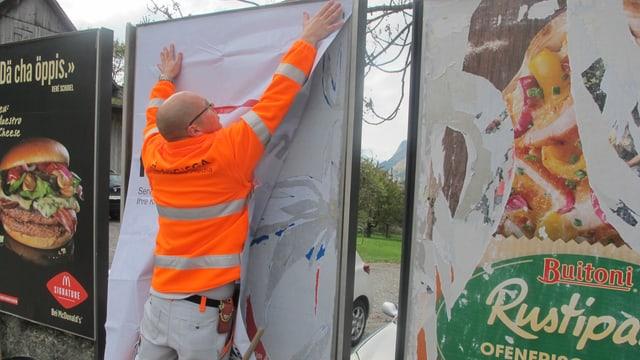 Ein Mann klebt ein Plakat an eine Plakatwand.