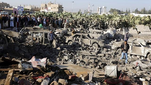 Autowracks in einem Quartier der Hautpstadt Sanaa, Zuschauer im Hintergrund.