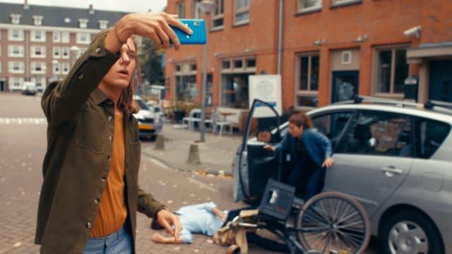 Ein junger Mann filmt sich mit einem Handy selbst. Hinter im ein Auto, neben dem ein verletzter Mann am Boden liegt.