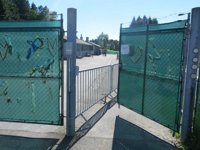 Ein halboffenes Gittertor bietet Einblick auf einen asphaltierten Platz.