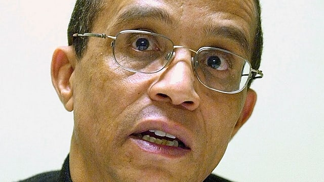 Ein Mann mit bräunlichem Hautteint und Brille, den Mund leicht geöffnet.