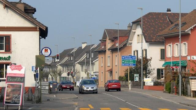 Eine Strasse durch die Gemeinde Augst, links und rechts Dorfhäuser.