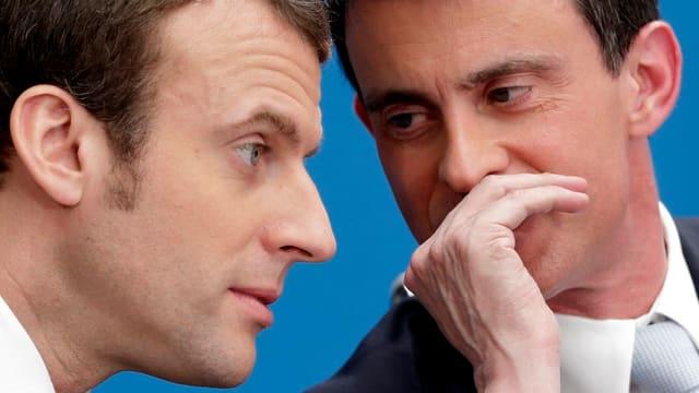 Purtret da Emmanuel Macron e Manuel Vals che scuttinan insatge.