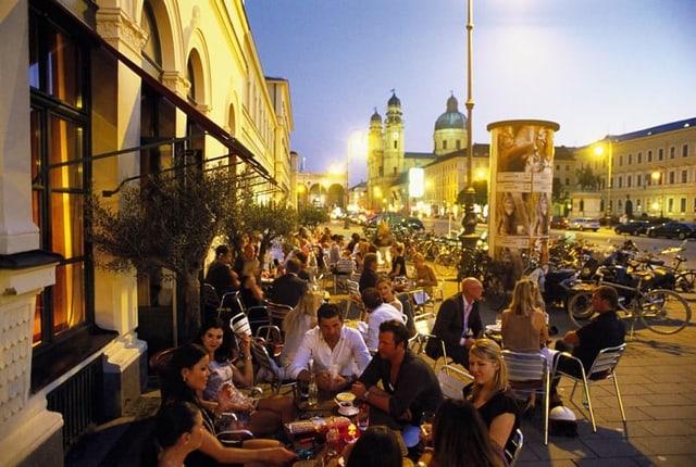 Menschenmenge sitzt vor einer Bar in München