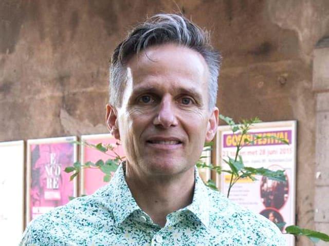 Christian Müller in grün-weiss-geblümbtem Hemd vor einer Mauer mit Plakaten