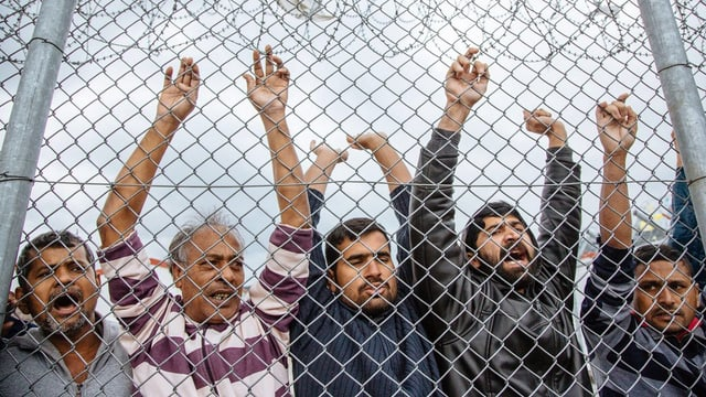 Männer hinter einem Zaun.