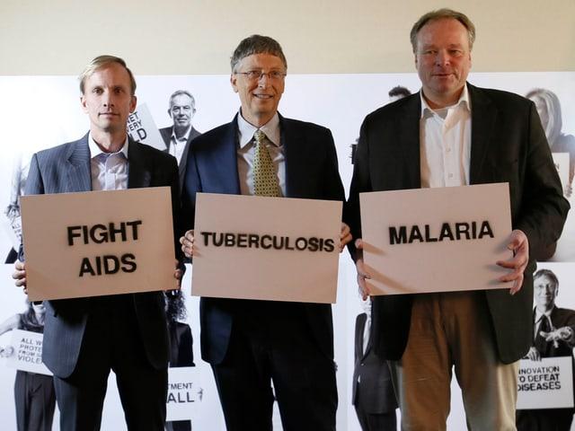 Mark Dybul, Bill Gates und Dirk Niebel halten Schilder mit den Worten «Fight Aids, Tuberkulose, Malaria» auf