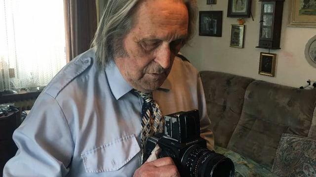 Ein älterer Mann hält eine Kamera.