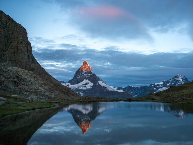 Das Matterhorn wird von der Sonne beschienen und spiegelt sich im Vordergrund im Bergsee.