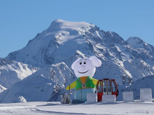 Am Skisammelplatz steht eine rote Gondel und eine mit Luft gefüllte Märchenfigur, es herrschen klare, wolkenlose Bedingungen.