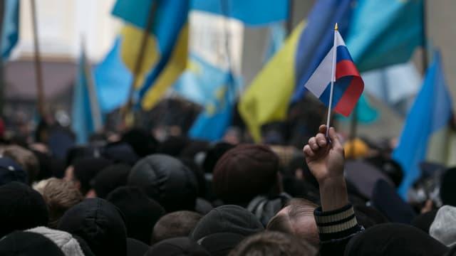 Demonstration in Simferopol vom 26.Februar - viele ukrainische Flaggen im Hintergrund, im Vordergrund streckt ein Demonstrant ein russisches Fähnchen in die Höhe.