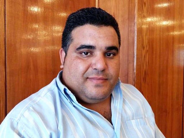 Ein beleibter Mann mit schwarzem, kurzem Haar und markanten dunklen Augsbrauen.