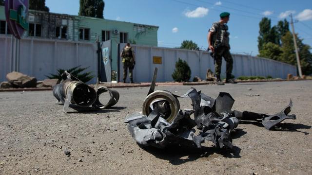 Soldaten stehen vor einem Grenzposten, am Boden liegen Waffen-Bruchstücke