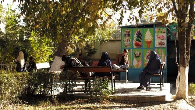 Frauen unter einem Baum vor einer Eisdiele geniessen ein Eis.