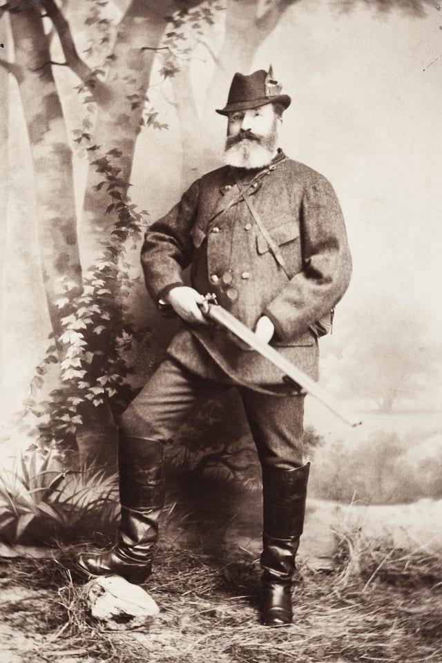 Hans von Hallwyl posiert in Jagdmontur mit Gewehr