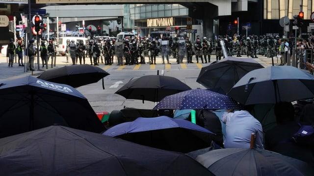Purtret da demonstrants che tegnan parasols entamaun, visavi ad els stattan duas colonnas da polizists e quai amez la citad da Hongkong.