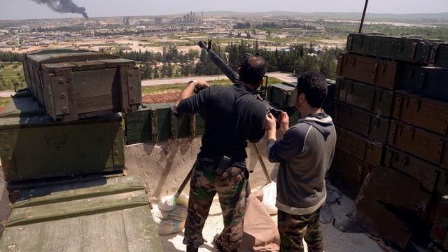 Zwei bewaffnete Männer auf einem Dach nahe Aleppo.