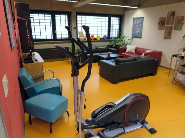 Ein Aufenthaltsraum. Hinten rechts stehen Ledersofas in der Ecke, an der Wand ein TV, im Vordergrund ein Fitnessgerät.