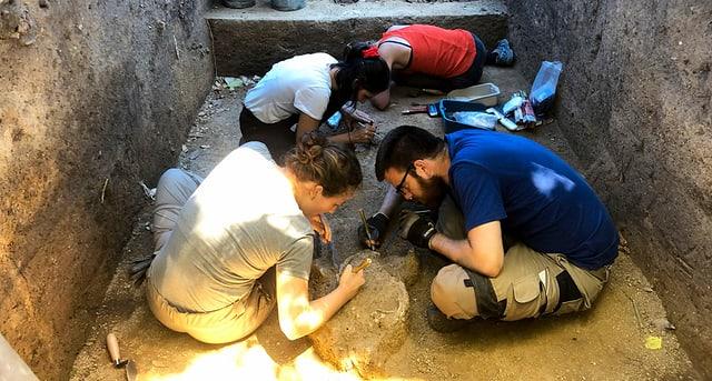 Archäologen arbeiten in einem Graben