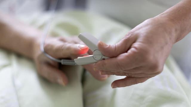 Die Hand einer Patientin und die Hand einer Pflegerin