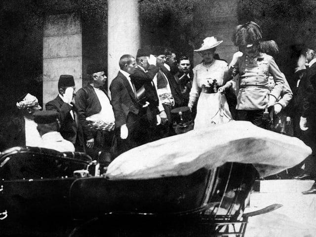 Schwarzweissfoto: Franz Ferdinand in Uniform steigt mmit seiner Frau in ein Auto.
