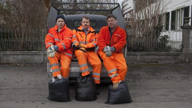 Die drei Abfalldetektive sitzen auf der Ablage eines Lieferwagens, ihre Füsse links sind jeweils auf einem Anfallsack positioniert.