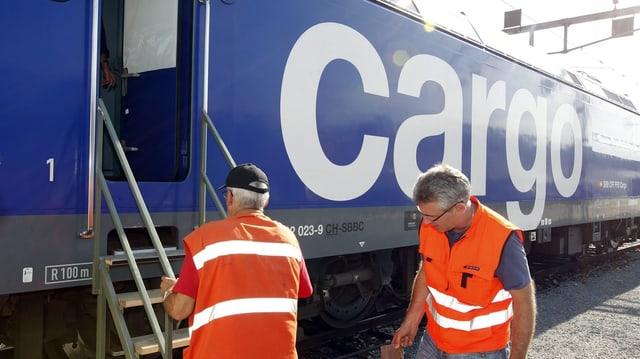 Waggon der SBB Cargo International mit zwei Menschen davor.