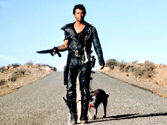 Mad Max steht auf der offenen Strasse mit einem Dolch in der Hand, hinter ihm ein Hund.