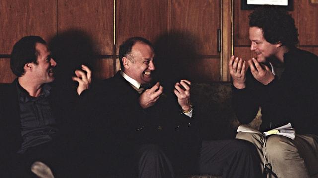Drei Männer sitzen vor vor einer dunklen Holzwand und diskutieren.