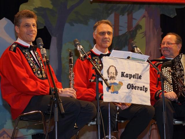 Drei Musikanten in roten Sennenkutten während einer Spielpause auf der Bühne.